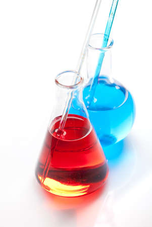 Two glass flasks - Clear liquid mixed with a colored chemical reagent, close-up view photo