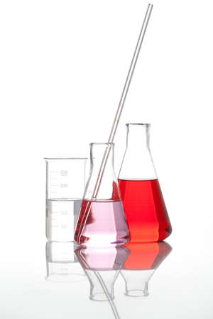 dropping: Glass flasks - Clear liquid mixed with a red colored chemical reagent, isolated
