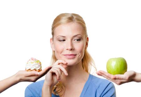 Hermosa mujer hace una elección difícil entre la torta y la manzana, aislado en blanco