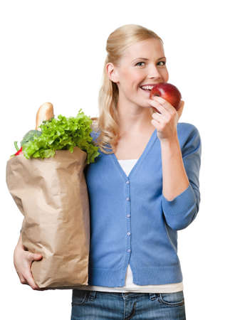 Pretty woman with a paper bag full of healthy food, isolated on white photo