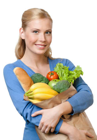 Young woman with a paper bag full of healthy food, isolated on white photo