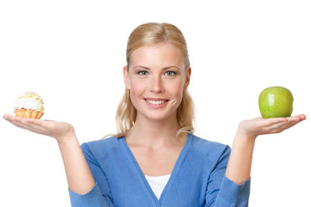 decide deciding: Attractive woman makes a tough choice between cake and apple, isolated on white Stock Photo