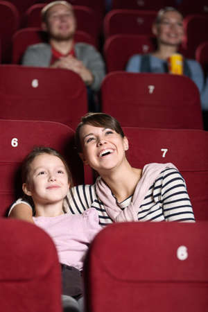 theater seat: Young with her mother watching a movie at the cinema