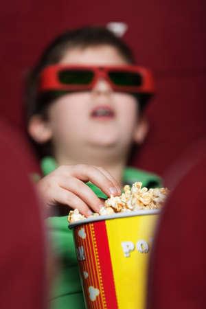 Un ni�o comiendo palomitas en el cine Foto de archivo - 13994404
