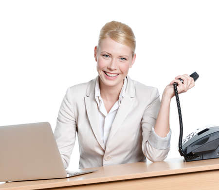 Young businesswoman sitting at a table and holding phone handset, isolated photo