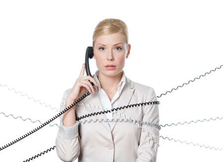 Young businesswoman sitting at a desk tied with phone cord, isolated photo