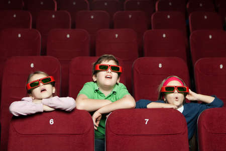 watching movie: Surprised children watching a movie  at the 3D cinema Stock Photo