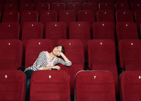 sits on a chair: Napping woman after the movie at the cinema