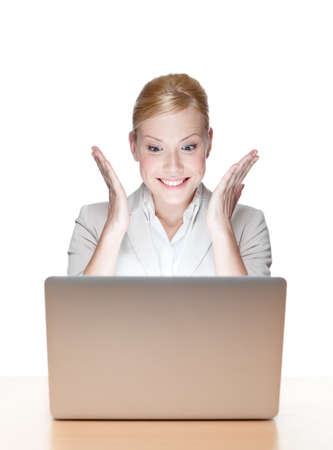 look pleased: Happy young business woman sitting at a office desk with laptop, isolated