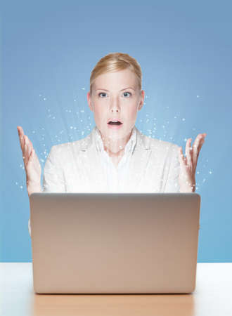 Attractive businesswoman with laptop, rays of light coming out of the laptop screen photo