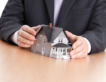 hands holding house: Real estate concept - businessman hands around household architectural model Stock Photo