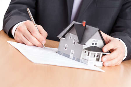 hand holding house: Real estate concept - business man signs contract behind home architectural model