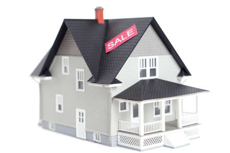 Real estate concept - home architectural model with sale sign, isolated Stock Photo - 13992205