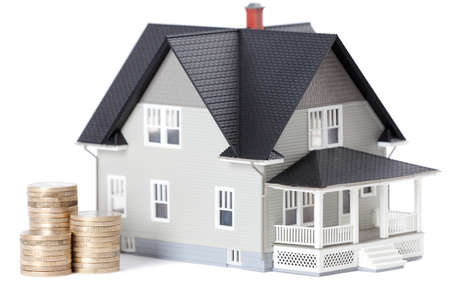 gold house: Real estate concept - stacks of coins in front of home architectural model, isolated