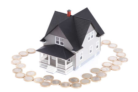 Real estate concept - coins around the home architectural model, isolated Stock Photo - 13999824