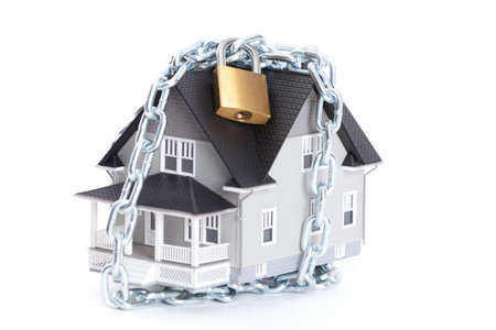 home safety: Real estate concept - chain with lock around the home architectural model, isolated