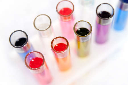 reagents: Group of laboratory test tubes with a colored reagents in a rack, isolated