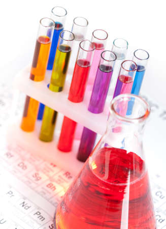 Group of test tubes and flask with colored liquids on the periodic table photo