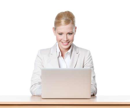 Glimlachend jonge zakenvrouw zittend aan een bureau tafel met laptop, geïsoleerd Stockfoto