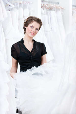 Shop assistant try to select a proper dress for the client, on white background photo
