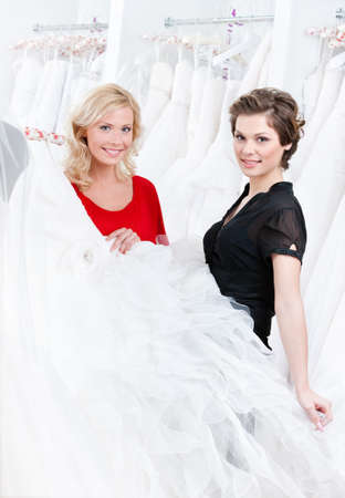 bridal salon: Bride is ready to try this wedding gown on, white background