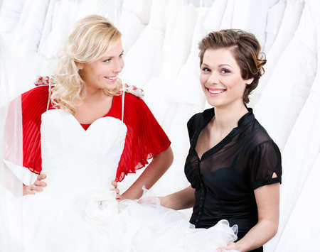 Hesitating about the wedding gown  Shop assistant persuades her Stock Photo - 14463005