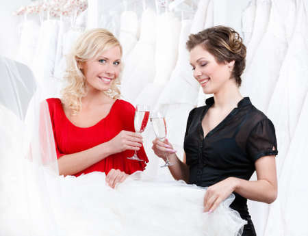 Two girls drink champagne or wine while discussing and choosing the wedding gown photo