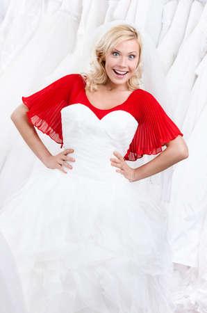 decides: Bride admires her wedding dress, white background