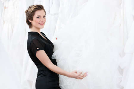 Shop assistant  is looking for the particular dress for the bride Stock Photo - 14462998