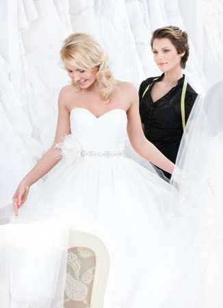 Girl admires the wedding dress that suits her, on white background photo