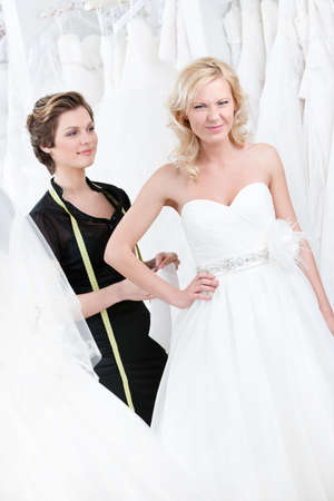 decides: Seamstress measures waist of the dissatisfied bride to fit the dress Stock Photo