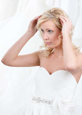 Charming bride puts tiara on her head, white background photo