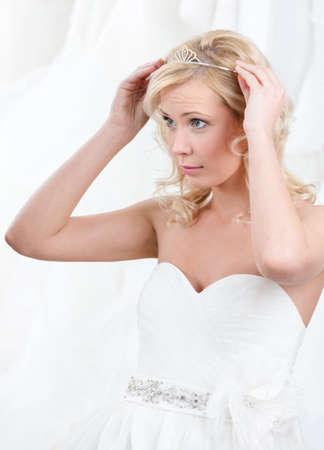Charming bride puts tiara on her head, white background photo