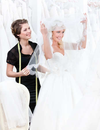 shot put: Shop assistant helps to the bride to put the wedding gown on  Bride raises the veil