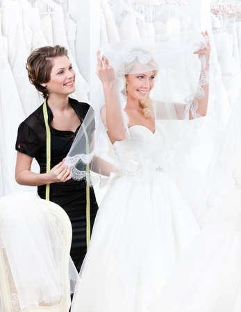 lanzamiento de bala: Tienda asistente ayuda a la novia a poner el vestido de novia de la novia levanta el velo Foto de archivo