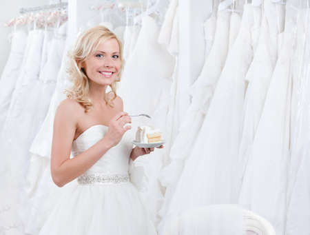 girl in red dress: Happy bride tastes wedding cake