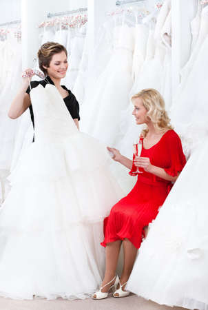 proposes: Shop assistant proposes another dress to the bride while she is drinking champagne Stock Photo