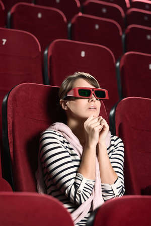 Young woman watching a horror at the cinema photo