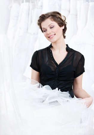 selects: Commesso sceglie un abito appropriato per il cliente, su sfondo bianco