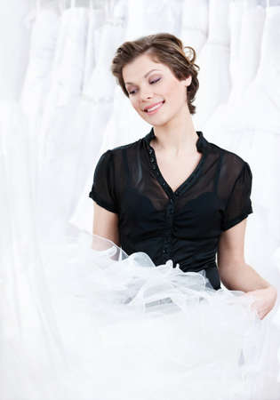 Shop assistant selects a proper dress for the client, on white background photo