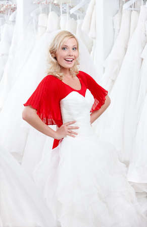 Young girl puts a wedding dress to her body, deciding whether it suits for her or not photo