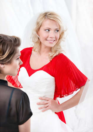 hard look: Bride puts the wedding gown to hesitating whether she should try it on or not Stock Photo