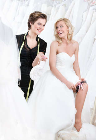 Shop assistant gives some piece of advice while future bride in wedding gown puts the garter photo