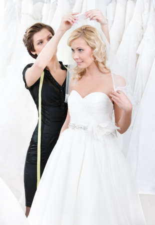 Shop assistant helps to the bride to fix the wedding veil photo