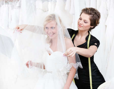 making dresses: Shop assistant sets the veil of the bride, white background