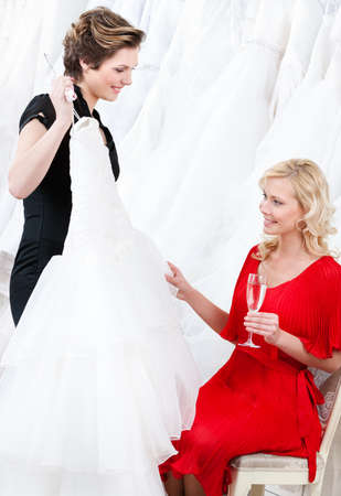proposes: Shop assistant proposes a wedding dress to the bride  She feels soft and pleasant material