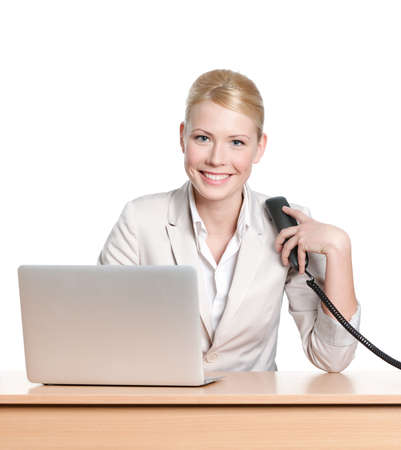 Young businesswoman sitting at a office desk and holding phone handset, isolated photo