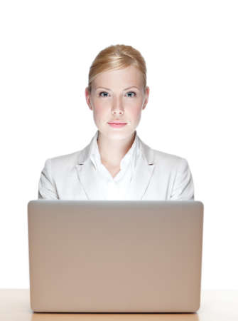 seriously: Young business woman sitting at a table with laptop, looking at the camera
