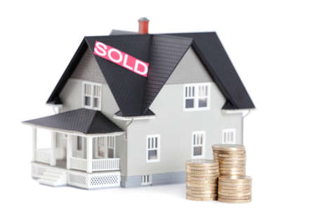 Real estate concept - stacks of coins in front of household architectural model, isolated Stock Photo - 14518026
