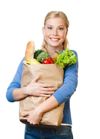 Beautiful woman with a paper bag full of healthy eating, isolated on white photo